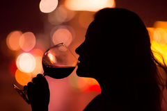 Silhouette of woman holding glass with wine. Royalty Free Stock Image