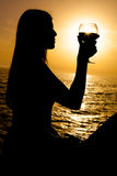 Silhouette of woman holding glass of wine during sunset on the ocean Royalty Free Stock Photo