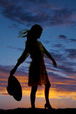 Silhouette of woman holding hat back wind Stock Image