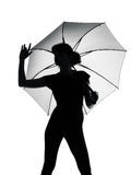 Silhouette woman holding open umbrella Stock Photos