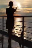 Silhouette of woman holding sun, standing on deck. Dark silhouette of woman holding sun and standing on deck at sunset Stock Photo