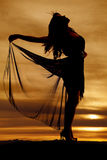 Silhouette woman holding up flowing skirt royalty free stock image