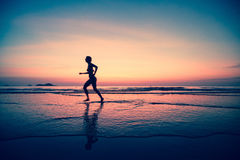 Silhouette of a woman jogger on the beach at sunset. In a surreal style Royalty Free Stock Images