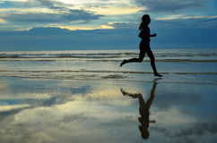 Silhouette of woman jogger running on sunset beach. With reflection, fitness and healthy life concept Stock Image