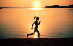 Silhouette woman jogging on beach Royalty Free Stock Photos