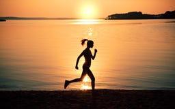 Silhouette woman jogging on beach royalty free stock photos