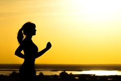 Silhouette of a woman jogging on nature at sunset, sports female profile, concept of sport, leisure and healthcare Stock Photo