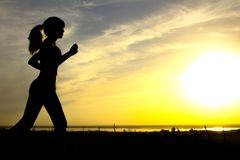 Silhouette of a woman jogging on nature at sunset, sports female profile, concept of sport, leisure and healthcare Stock Photos