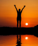 Silhouette woman jumping against orange sunset Stock Photo