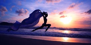 Silhouette of woman jumping on the beach Stock Photos