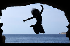 Silhouette of a woman jumping on the beach Stock Photo