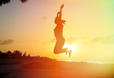 Silhouette of woman jumping on beach Royalty Free Stock Images