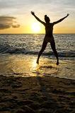 Sunset Silhouette. Silhouette of a woman jumping on the beach at sunset Royalty Free Stock Image