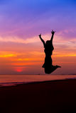 Silhouette of woman jumping with hands up and showing I LOVE YOU Stock Photos