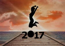 Silhouette of woman jumping over 2017 new year sign. On beach dock Royalty Free Stock Images