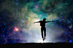 Silhouette of a woman jumping, starry night royalty free stock image