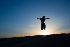 Silhouette of a woman jumping Stock Photo