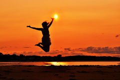 Silhouette of a woman jumping at sunset, touching. A silhouette of a woman in a dress jumping high in the air at the ocean, reaching and touching the sun Stock Images