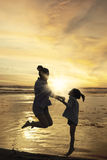 Silhouette woman and kid jump at coast Royalty Free Stock Photography