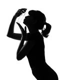 Silhouette woman kissing her perfume Royalty Free Stock Images