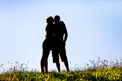 Silhouette of a woman kissing a man Stock Photos