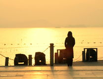 Silhouette of woman by lake. Rear view silhouette of woman stood at picturesque lake during colorful sunset, West Lake, Hangzhou, China Stock Photo