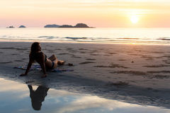 Silhouette of woman laying on sunset sea beach. Stock Photos