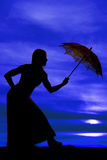Silhouette of a woman lean over with umbrella blue sky royalty free stock images
