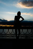 A silhouette of a woman leaning back against fence Royalty Free Stock Photo