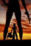 Silhouette of woman legs back bikini bottoms holding gun Stock Image