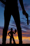 Silhouette of a woman legs in boots holding gun cowboy between l. A woman holding on to a pistol, with a cowboy inbetween her legs stock image