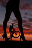Silhouette woman legs face side man on bike Stock Photo