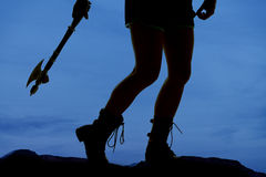 Silhouette woman legs hatchet behind. A silhouette of a woman's legs holding on to a hatchet Royalty Free Stock Image