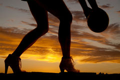Silhouette woman legs hold ball to side Royalty Free Stock Photography