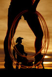 Silhouette woman legs rope side. A silhouette of a woman holding on to a rope with a cowboy inbetween her legs Royalty Free Stock Photos