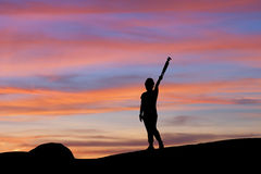 Silhouette of woman lifting tripod under the sky at sunset Royalty Free Stock Photo
