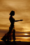 Silhouette woman long dress reach Stock Photo