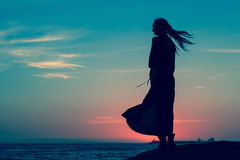 Silhouette of woman in long dress standing on the seashore after sundown. Nature. Royalty Free Stock Image
