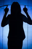 Silhouette of woman looking through the blind Royalty Free Stock Image
