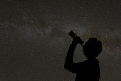 Silhouette of woman looking at stars. Woman looking through telescope at night sky Stock Photos