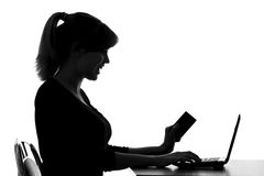 Silhouette of a woman makes online purchase at home Royalty Free Stock Images