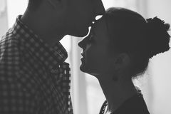 Silhouette of woman and man kissing Stock Images