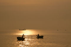 Silhouette of woman and man rowing in woven bamboo basket boat Stock Photos