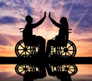 Concept of mutual aid people with disabilities. Silhouette of a woman and a man in a wheelchair, support each other and their reflection in the water. The Royalty Free Stock Photography