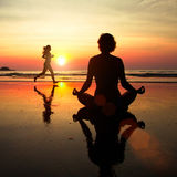 Silhouette of a woman meditating on the beach at sunset, woman jogger in the background. Stock Photos