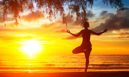 Silhouette of woman meditating on the beach. Yoga. Stock Images
