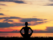 Silhouette of a woman meditating on red Royalty Free Stock Photography