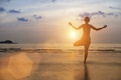 Silhouette of woman meditating on the sea beach. Royalty Free Stock Photo
