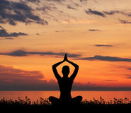 Silhouette of a woman meditating on a sunset Stock Images