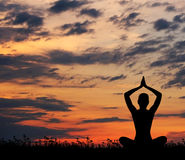 Silhouette of a woman meditating on a sunset Stock Photos